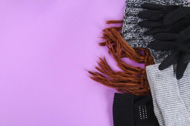 Roupas de inverno e outono, chapéus, cachecóis, luvas em um fundo roxo pastel.