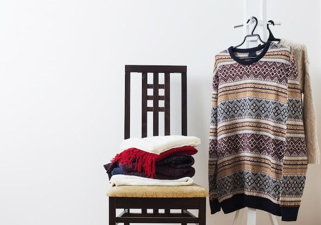 Roupas de inverno em uma cadeira contra uma parede branca