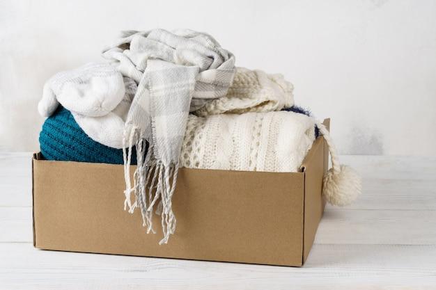 Roupas de inverno em uma caixa de papelão. roupas sazonais para envio ou doação.
