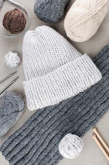 Roupas de malha e bobinas de lã sobre a textura