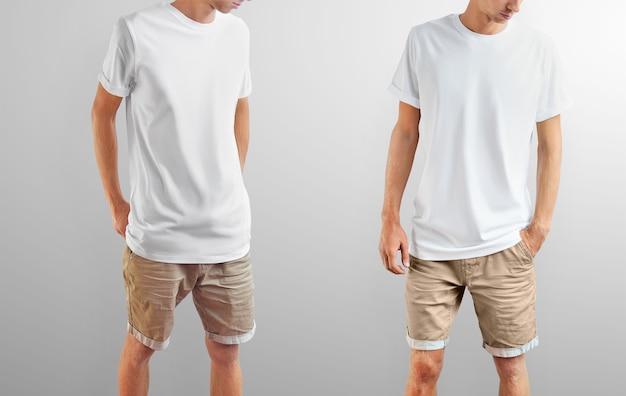 Roupas de maquete. cara de slim fit em uma camiseta branca e shorts marrons em um isolado em um fundo cinza do estúdio. duas poses na imagem. modelo pronto para você projetar.