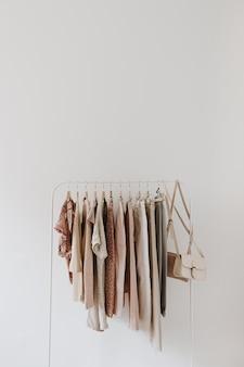 Roupas de moda feminina em tons pastel brilhantes em cabide branco