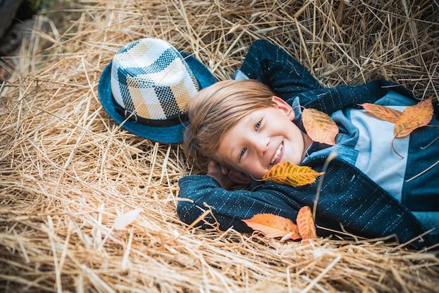 Roupas de outono e crianças coloridas tendências menino em uma brisa em uma vila de outono menino de criança de outono com conceito de anúncio de humor outonal
