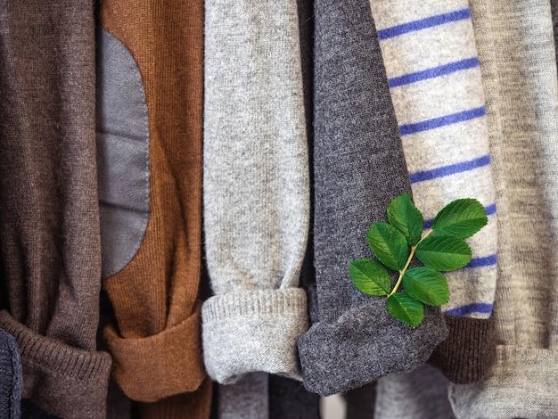Roupas de outono e inverno penduradas em cabides no camarim. sem pessoas, close-up. conceito de beleza e moda
