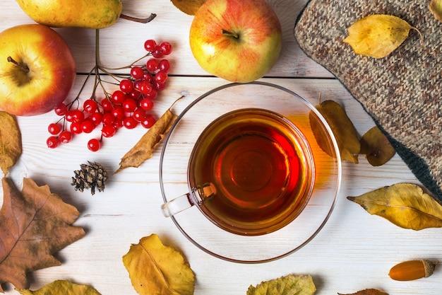 Roupas de outono e uma xícara de chá em um fundo de madeira