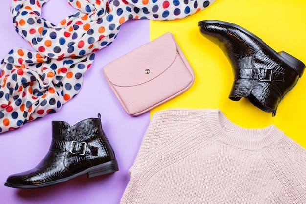 Roupas de outono femininas na moda. botas elegantes, camisola rosa, bolsa rosa e cachecol impresso sobre um fundo brilhante
