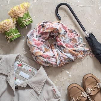 Roupas de outono feminino. roupa feminina de outono. grupo de saco, acessórios - sapatas e lenço no fundo marrom de madeira da tabela. vista de cima, copie o espaço