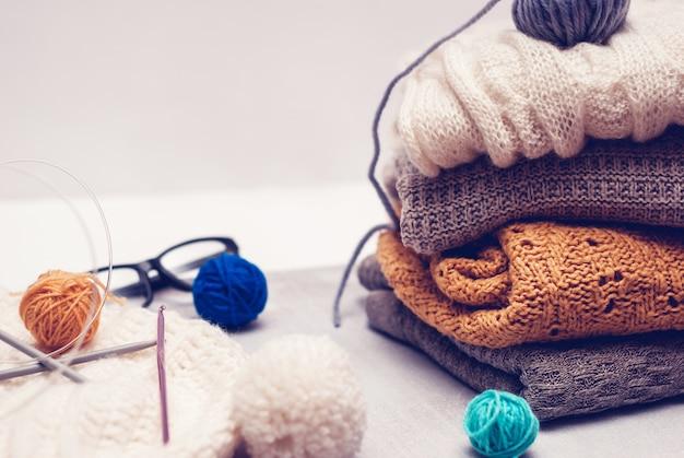 Roupas de tricô quente e clews de fios no fundo branco