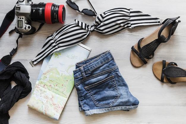 Roupas de viagem femininas com câmera e mapa na mesa