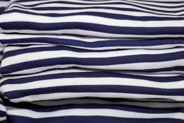 Roupas dobradas em uma pilha - camisetas listradas passadas a ferro.