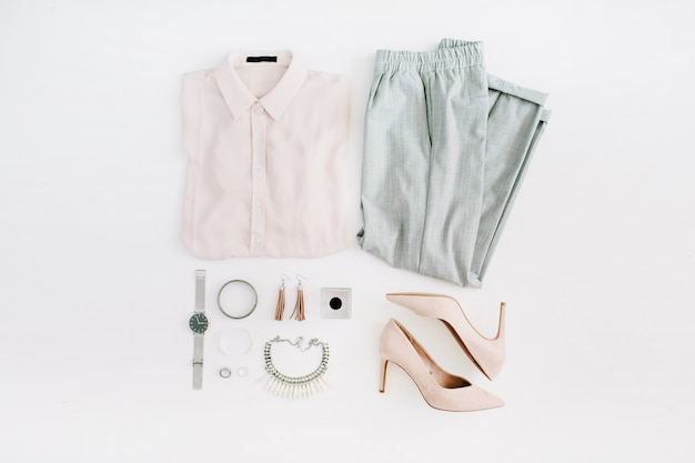 Roupas e acessórios da moda. look de estilo casual feminino liso com blusa pastel, calças, salto alto, relógio, perfume, colar, brincos. vista do topo.