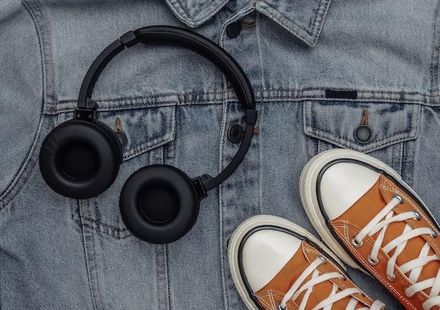 Roupas e acessórios juvenis. tênis e fones de ouvido no fundo da jaqueta jeans. vista do topo. postura plana