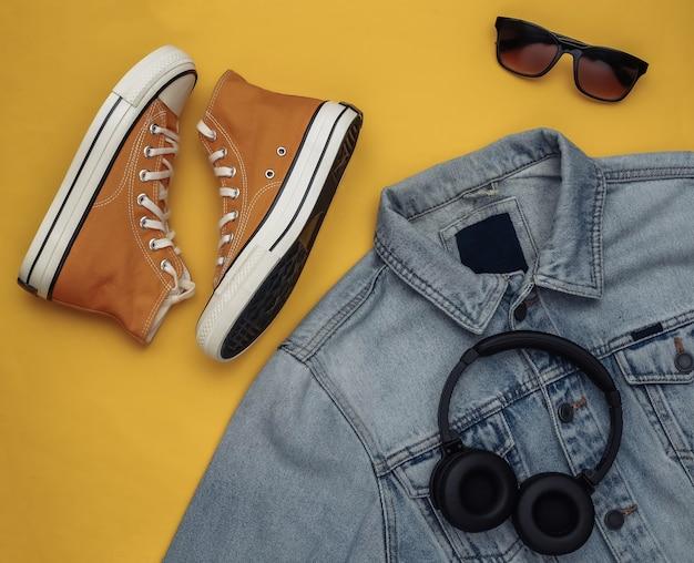 Roupas e acessórios juvenis. tênis, jaqueta jeans, óculos escuros e fones de ouvido em fundo amarelo. vista do topo. postura plana