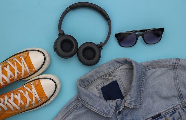 Roupas e acessórios juvenis. tênis, jaqueta jeans, óculos escuros e fones de ouvido em fundo azul. vista do topo. postura plana
