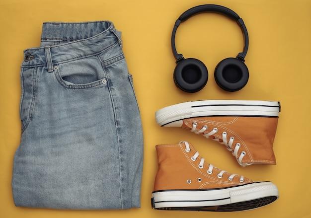 Roupas e acessórios juvenis. tênis, jeans e fones de ouvido em um fundo amarelo. vista do topo. postura plana