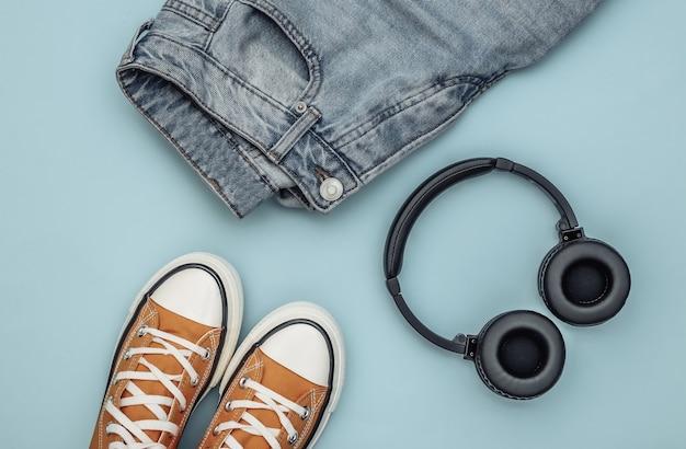 Roupas e acessórios juvenis. tênis, jeans e fones de ouvido sobre fundo azul. vista do topo. postura plana