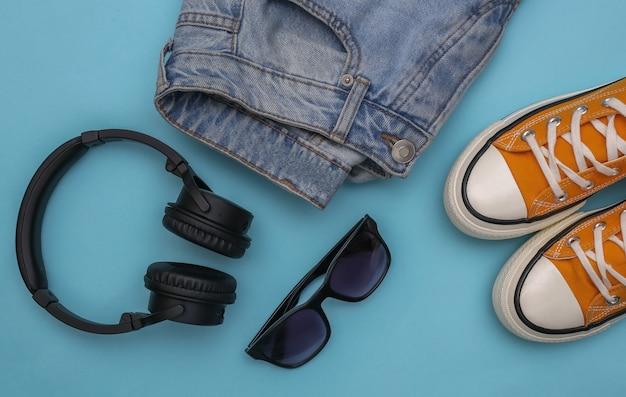 Roupas e acessórios juvenis. tênis, jeans, óculos escuros e fones de ouvido em fundo azul. vista do topo. postura plana