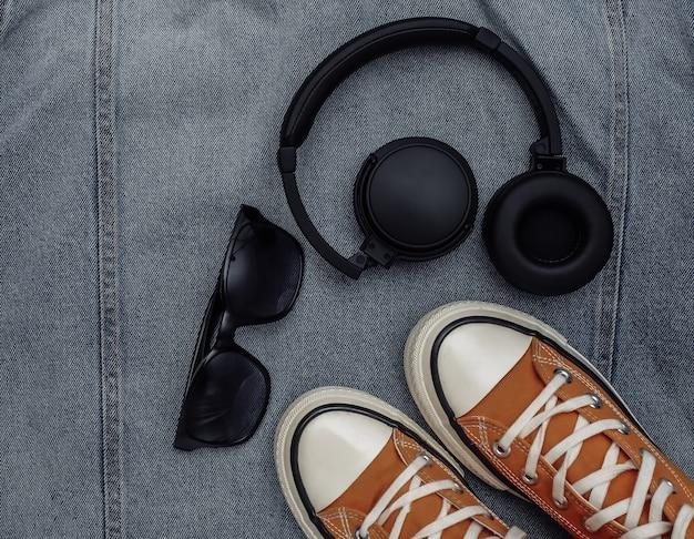Roupas e acessórios juvenis. tênis, óculos escuros e fones de ouvido no fundo da jaqueta jeans. vista do topo. postura plana