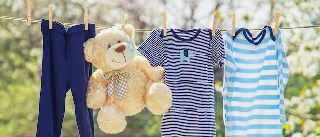 Roupas e acessórios para bebês pesam na corda após serem lavados ao ar livre.