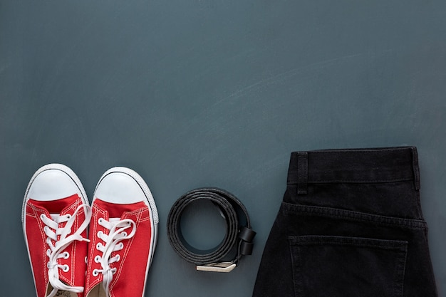 Roupas elegantes. vista superior do cinto de couro preto na moda, calça jeans preta e tênis juventude vermelho sobre fundo cinza de madeira.