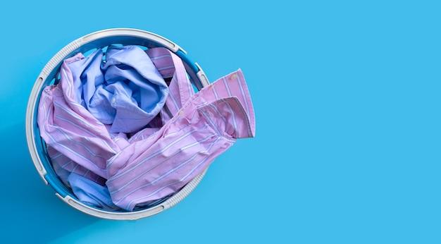 Roupas em um cesto de roupa suja em azul.
