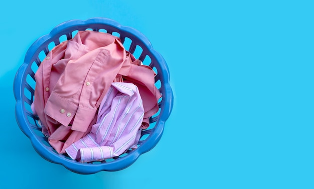 Roupas em um cesto de roupa suja no espaço azul. copie o espaço