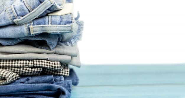Roupas empilhadas e calças em branco isolado