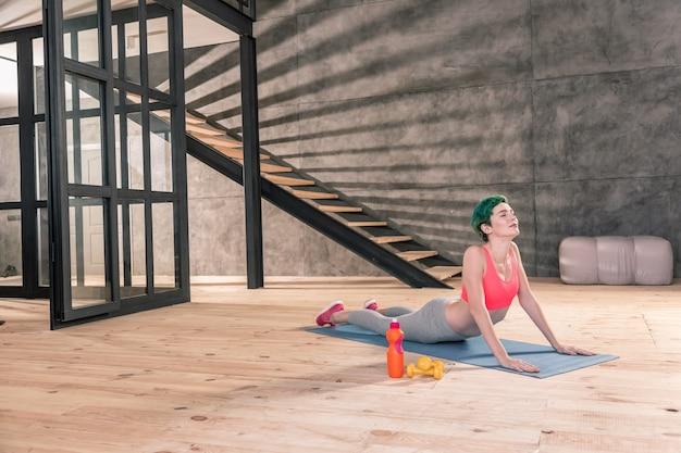 Roupas esportivas. mulher magra com cabelo verde, vestindo roupas esportivas e se alongando após um treino intenso
