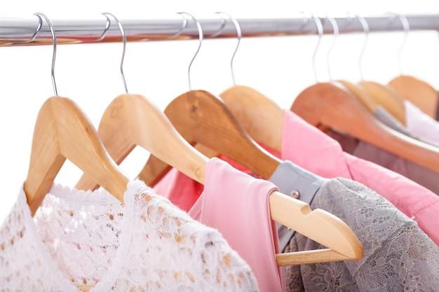 Roupas femininas cinza e rosa em cabides de madeira em um rack em fundo branco. guarda-roupa feminino