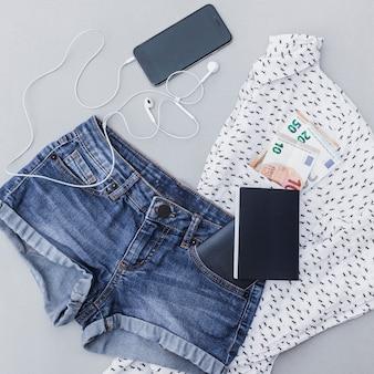 Roupas femininas com nota móvel, euro e passaporte em fundo cinza
