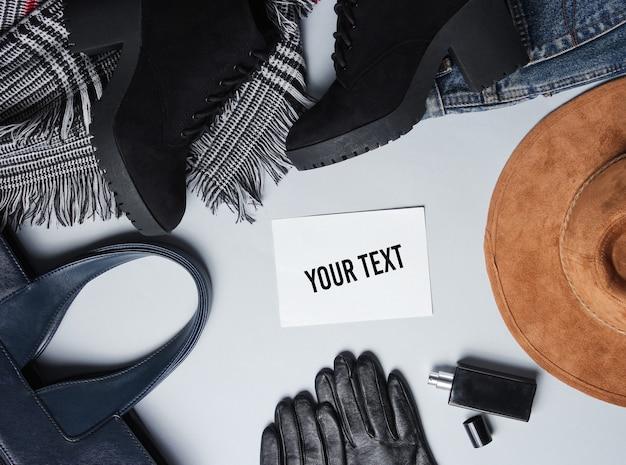 Roupas femininas da moda, sapatos, acessórios e um pedaço de papel branco para sua informação sobre fundo cinza. vista do topo. copie o espaço. estilo liso