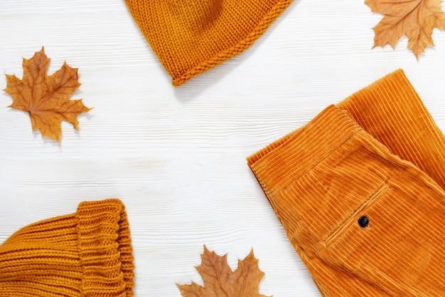 Roupas femininas de outono, cachecol de malha quente e boné de cor laranja e calças de veludo.