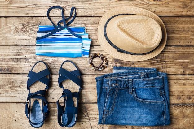 Roupas femininas de verão. foto de moda plana leigos. blue jeans, t-shirt, chapéu de sol, sandálias azuis sobre fundo de madeira.