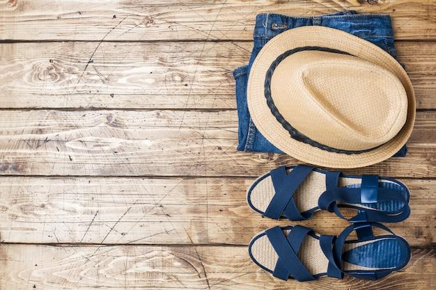 Roupas femininas de verão. foto de moda plana leigos. calças de ganga, chapéu do sol, sandálias azuis no fundo de madeira.