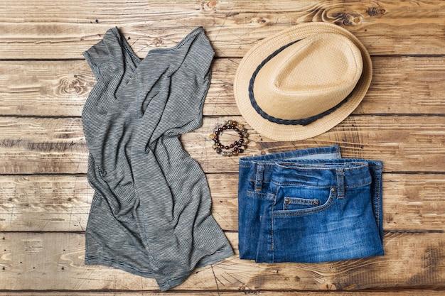 Roupas femininas de verão. foto de moda plana leigos. calças de ganga, t-shirt, chapéu de sol no fundo de madeira.