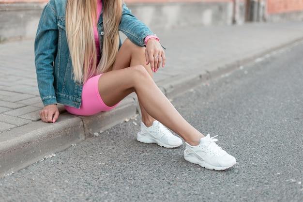 Roupas femininas elegantes. sapatos femininos da moda. design casual. close-up de uma jovem loira de tênis na moda de couro branco com uma jaqueta jeans em shorts rosa glamourosos. estilo de rua.