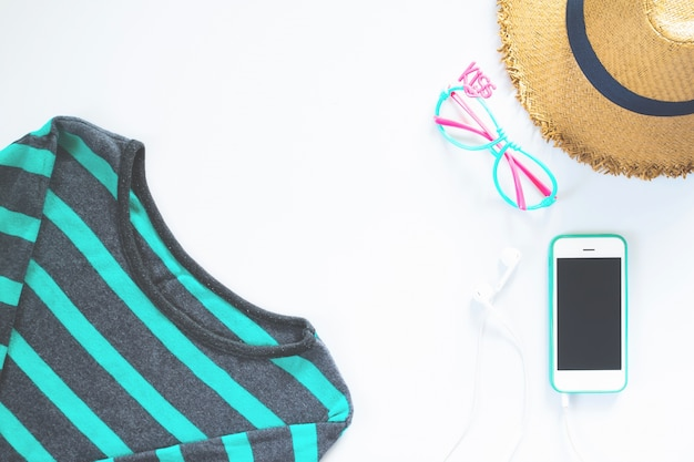 Roupas femininas lisas e colagem de acessórios com t-shirt, óculos de moda, chapéu com telefone celular e fone de ouvido no fundo branco.