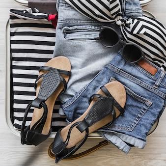 Roupas femininas, óculos escuros e par de sandália na bolsa de viagem