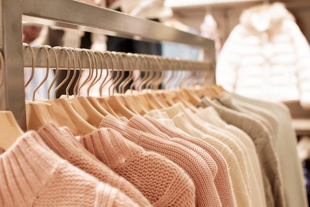 Roupas femininas rosa em cabides de madeira em prateleiras em loja de moda
