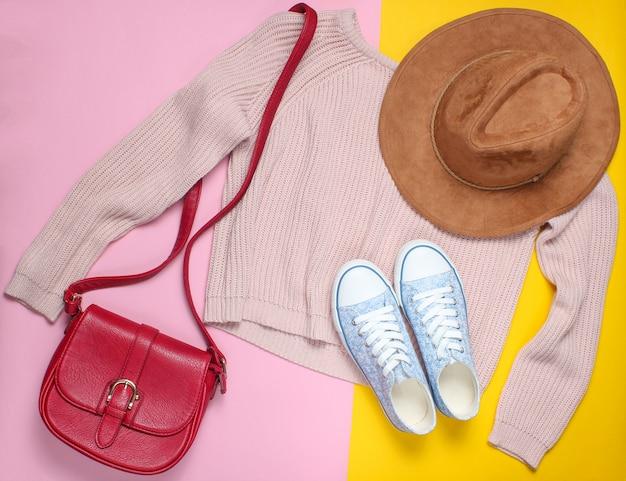 Roupas femininas, sapatos, acessórios em tons pastel. camisola, bolsa de couro, tênis, chapéu de feltro. vista do topo