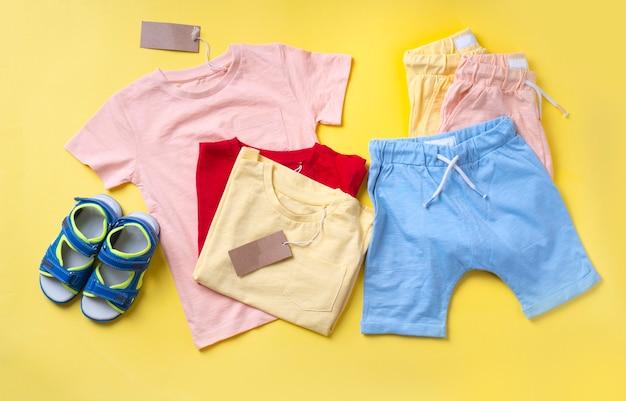 Roupas infantis, camisetas, shorts e sandálias no parque amarelo