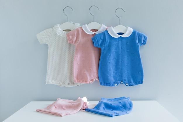 Roupas infantis na linha de roupa contra o fundo de madeira