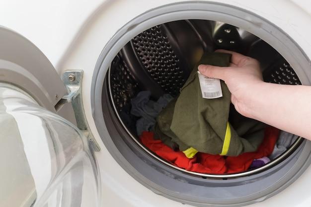 Roupas infantis sujas na máquina de lavar. mulher olha para a etiqueta da camiseta infantil
