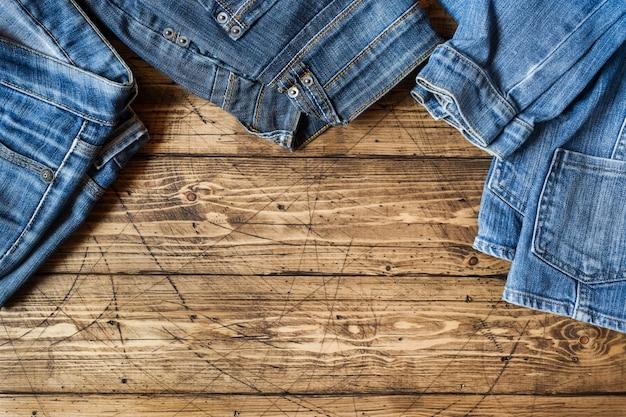 Roupas jeans e acessórios na superfície de madeira marrom