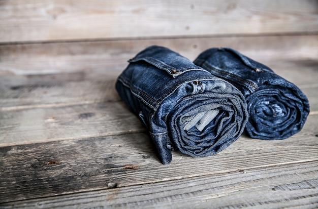 Roupas. jeans torcidos em uma mesa de madeira