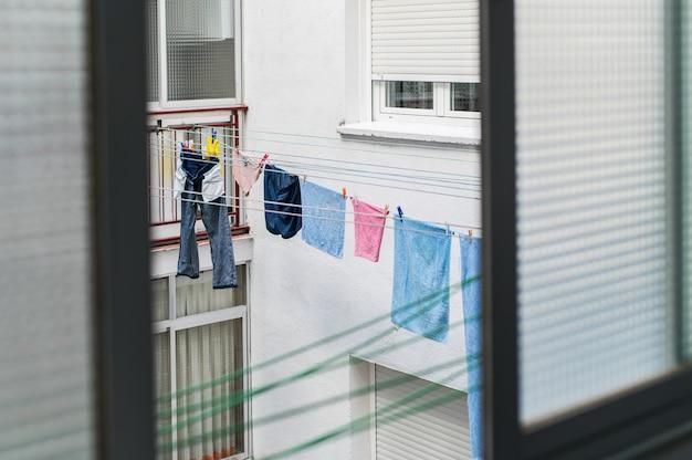 Roupas lavadas de cima na varanda do prédio urbano