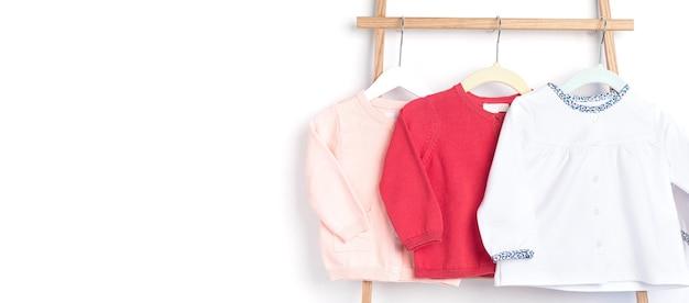 Roupas lindas para recém-nascidos penduradas na prateleira