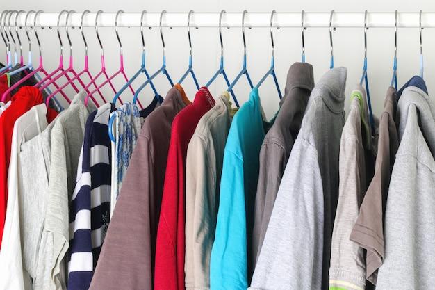 Roupas masculinas e femininas em cabides de silicone no guarda-roupa. mesmos ombros. organização de armazenamento. ordem e limpeza. quarentena, auto-isolamento, trabalho doméstico. precisão.