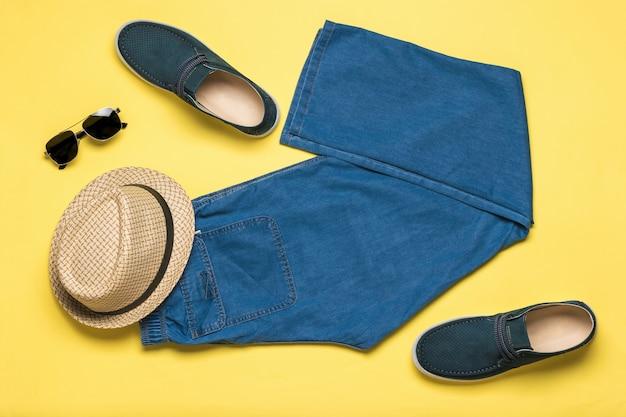 Roupas masculinas e sapatos para as férias de verão em uma superfície amarela. espaço para o texto. postura plana.