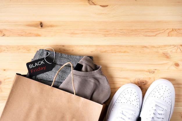 Roupas masculinas elegantes em um saco de papel e sapatos brancos com uma placa preta de sexta-feira em uma mesa de madeira